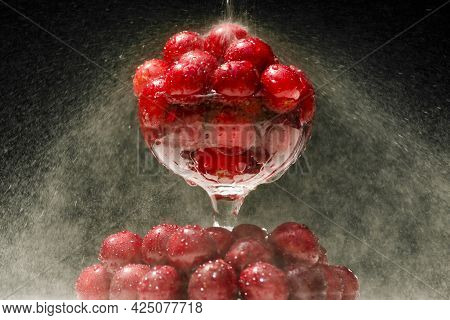 Ripe Cherries In A Glass. Juicy Cherries In A Glass With Splashing Water On A Black Background.