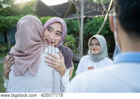 A Woman Wearing A Headscarf Hugs A Veiled Woman During A Gathering