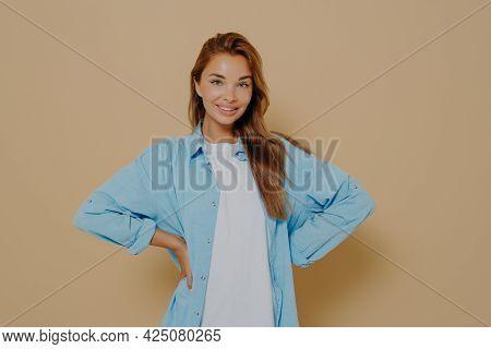 Self Assured Smiling Lovely Model Keeps Hands On Waist, Wears Long Blue Shirt Over White Tshirt, Loo
