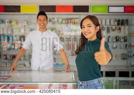 Beautiful Young Woman With Thumbs Up Standing Against The Background Of A Smartphone Shop