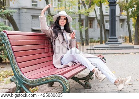 Woman With A Phone Sits On A Bench And Waves Her Hand Beckons To Her