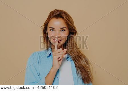 Portrait Of Joyful Smiling Female With Long Light Brown Hair Holding Index Finger At Her Lips, Sayin