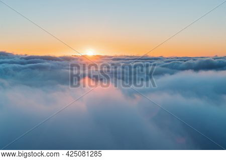 Beautiful Sky Backgound. Orange Sun Sets Behind Fluffy White Clouds. Amazing Sunset View Among Heaven. Beauty of Nature.