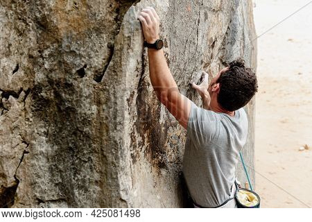 Young Caucasian Man With Smart Watch Overcoming Obstacles While Climbing On A Rock In The Mountain.