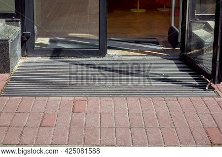 Entrance To The Store From A Pedestrian Sidewalk From A Plink On A Foot Mat Through A Glass Door, Th