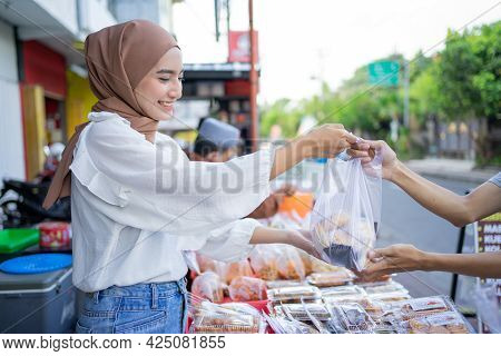 A Beautiful Girl In A Headscarf Gives Takjil Food Orders In Plastic Bags To Buyers