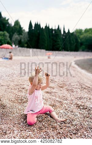 Little Girl Sits On A Pebble Beach And Throws Pebbles Up