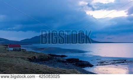 Scenic mountain landscape with dramatic sky and reflections in the lake in Iceland during night time.