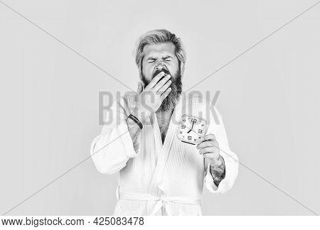 Noise Of Alarm Clock. Man Awake With Alarm Clock Ringing. Guy In Bathrobe. Sleepy Man Hold Alarm Clo