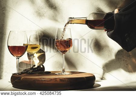 Wine Tasting. Rose Wine Pouring Into Glass On Background With Selection Of Red, White And Rose Wines