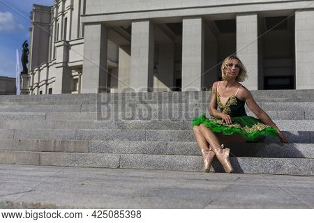 Dancing Concepts. Resting Professional Caucasian Ballet Dancer In Green Tutu Dress Posing On Stairs