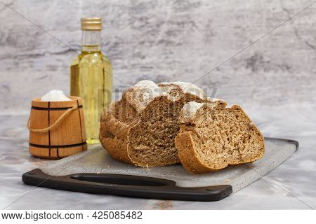 Loaf Of Rye Bread On A Cutting Board, A Bottle Of Sunflower Oil And A Wooden Salt Cellar On The Kitc