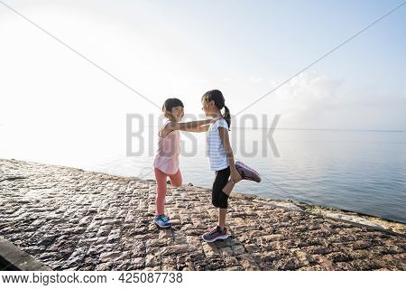 Athletic Young Kids Doing Stretching Legs Exercises Together