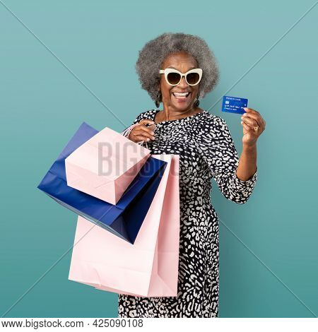 Cheerful black senior woman with shopping bags and a credit card mockup