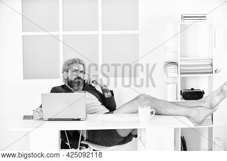 Good Deal. Teleworking Man In Home Office. Mature Businessman In Jacket Is Using Computer. Barefoot