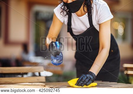 Disinfection Of A Cafe, Restaurant, Coffee Shop Before Opening. A Waitress Wearing A Protective Mask