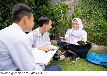 A Teenager Wearing A Headscarf In School Uniform Gave An Explanation By Holding A Book While Studyin