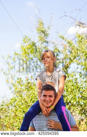 Defocused Brother Giving Sister Ride On Back. Portrait Of Happy Girl On Man Shoulders, Piggyback. Fa