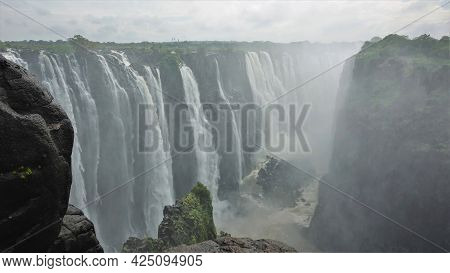 The Powerful Streams Of The Zambezi River Plunge Into The Abyss. The Fog Is Over The Gorge. Wet Boul
