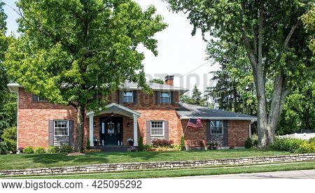 American Red Brick House with Large Mature Trees and Stone Retaining Wall
