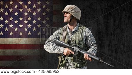 Composition of male soldier holding gun,looking away, against american flag on black. patriotism, independence and celebration concept digitally generated image.