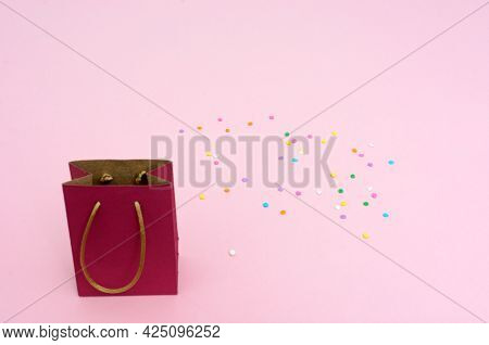 Small Red Gift Bag On Pink Background. Isolated Element.