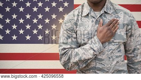 Composition of midsection of soldier with hand on heart, against american flag. patriotism, independence and military concept digitally generated image.