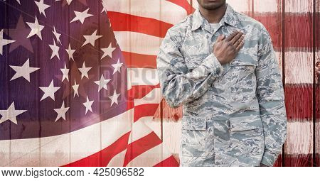 Composition of midsection of male soldier with hand on heart, against blowing american flag. patriotism, independence and military concept digitally generated image.