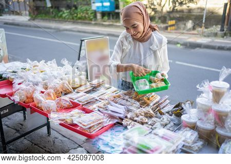 A Beautiful Girl In A Headscarf Holding A Plastic Tray To Put Fried Options Bought
