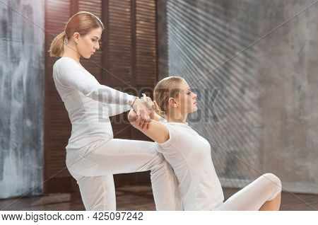Professional masseur doing Thai massage. Therapist is making body stretching exercises to the client in a traditional spa. Wellness and health care concept.