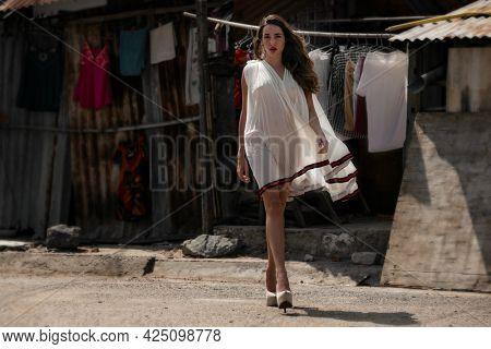 Urban portrait of gorgeous Young woman in brandy dress in vietnamese slum