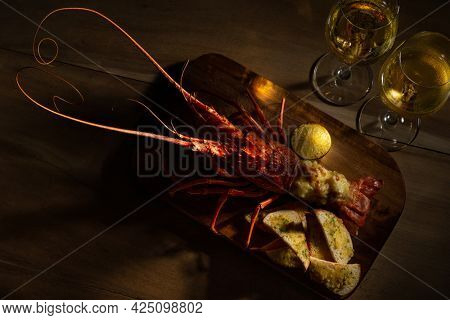 Romantic Dinner for Two. Red lobster with croutons and sauce and two glass of white wine on wooden surface with copy space