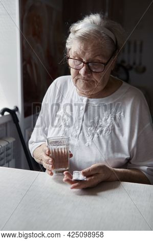 Sad old woman taking pills, health problems in old age, expensive medications. An elderly woman's ha