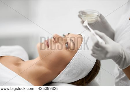 Side View Of Young Beautiful Brunette Woman Lying And Beautician In Rubber Gloves Doing Cleaning Fac