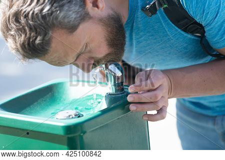 Water Aid Your Thirst. Thirsty Man. Guy Drink Water From Drinking Fountain. Thirst Quenching.
