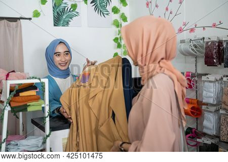 A Veiled Business Woman Receives A Customer-selected Outfit That Is Bought And Paid For At The Check