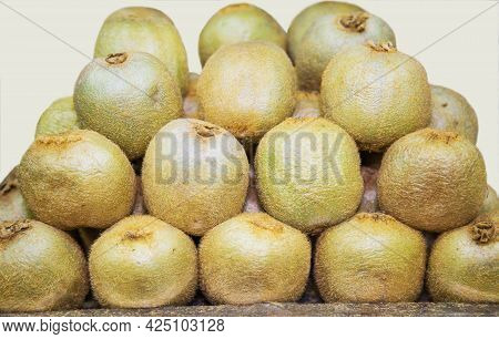 The Fruits Of Kiwi (latin Actinidia Chinensis) Are Green, Shaggy, Folded Into A Pyramid. Fruits Nuts