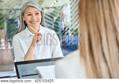 Senior Smiling Mature Asian Business Woman Training Young Intern Trainee At Meeting In Modern Office