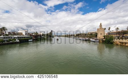 Seville, Spain - 08 April, 2019: View Of Guadalkivir River And Torre Del Oro, Historical Limestone T