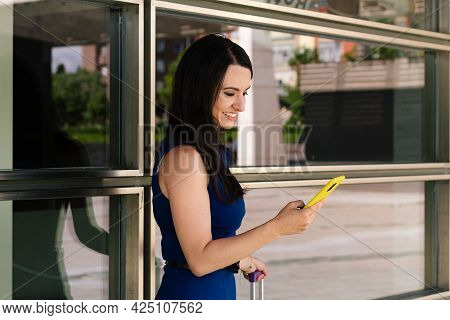 Successful Young Adult Woman Commuter Using Her Yellow Smartphone Waiting With Her Suitcase With A G