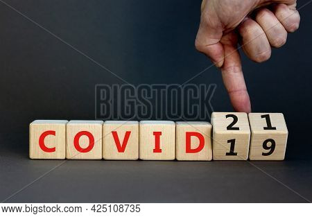 Symbol Of Covid-19 Pandemic In 2021 Year. Businessman Turns Wooden Cubes And Changes Words 'covid-19