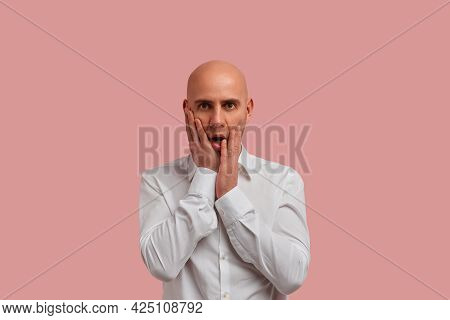 Wtf. Omg. Portrait Of Shocked Astonished Bald Guy With Bristle, Keeps Palms On Cheeks Having Wide Op