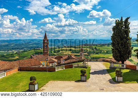 Old town of Govone overlooking green hills under beautiful blue sky with white clouds in Piedmont, Northern Italy.