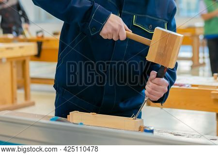 Professional Man Carpenter Using Chisel And Hammer To Carve Wood On Workbench At Workshop: Close Up.