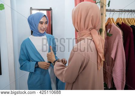 A Woman In A Veil Tries On Clothes In A Changing Room In Front Of The Mirror And Her Friend Complime