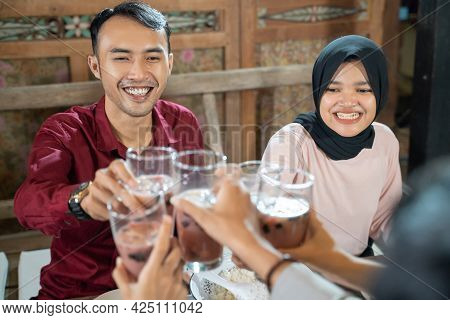 A Couple Of Young People Celebrate And Raise Glasses Of Fruit Ice For Toast While Breaking The Fast