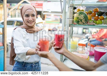 A Beautiful Girl In A Veil Smiled As She Took Two Cups Of Fruit Ice From The Seller