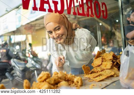 A Beautiful Girl In A Veil With Finger Pointing While Choosing Fried Food