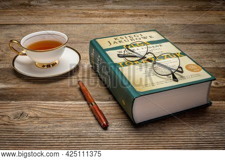 Fort Collins, CO, USA - June 27, 2021: The Books of Jacob (Polish edition), historical novel by Olga Tokarczuk with tea and reading glasses - 2018 Nobel Prize in literature.