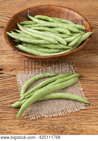 A Group Of Green Bean Pods In A Bowl Over Wooden Table.